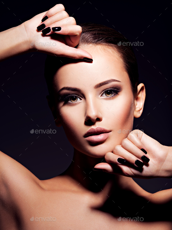 Face of a beautiful girl with fashion makeup and black nails - Stock Photo - Images