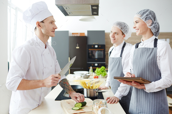 Positive young intern cooks asking chef at master class - Stock Photo - Images
