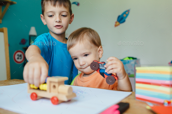 Two brothers playing together with toy cars - Stock Photo - Images