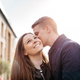A boyfriend whispering into his girlfriends ear while dating in the city. - PhotoDune Item for Sale
