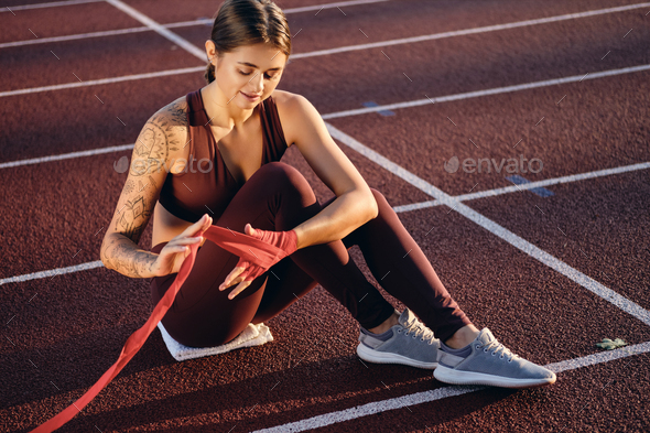 Athlete Girl With Tattooed Hand In Sportswear Wrapping Red Boxing Bandage On Hand On Stadium