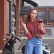 Young woman with colored pigtails using mobile phone on moped - PhotoDune Item for Sale