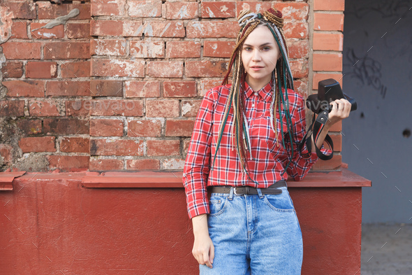 Hipster woman photographer with retro film camera on old brick wall - Stock Photo - Images