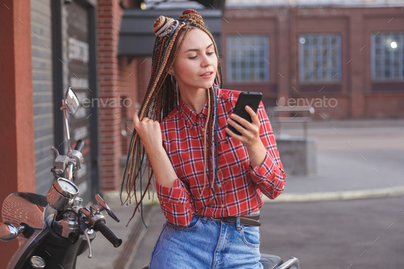 Young woman with colored pigtails using mobile phone on moped - Stock Photo - Images