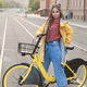 Young woman wearing yellow coat and colored pigtails, riding bike in city. - PhotoDune Item for Sale