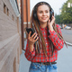Young woman with colored pigtails listening to music in headphones on the street - PhotoDune Item for Sale