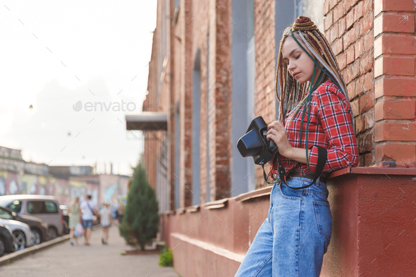 Hipster young photographer girl on the street with retro camera - Stock Photo - Images