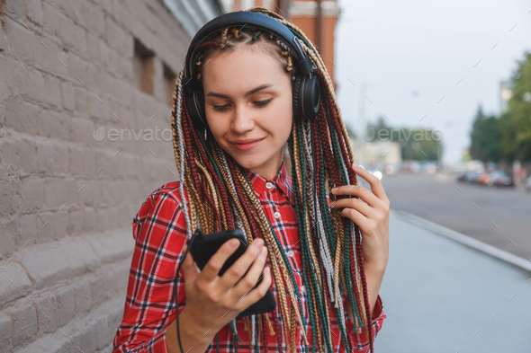 Young woman with colored pigtails listening to music in headphones on the street - Stock Photo - Images
