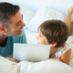 Middle-age father with her eight years daughter using digital tablet in bedroom - PhotoDune Item for Sale