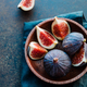 Macro photo of ripe figs in a wooden small bowl on a table. - PhotoDune Item for Sale