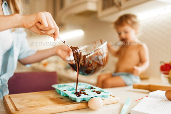 Mother and kid cooking and tastes melted chocolate - Stock Photo - Images