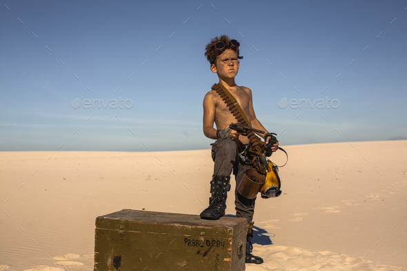 Post-apocalyptic boy outdoors in desert - Stock Photo - Images