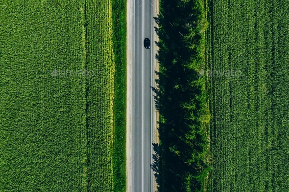Aerial view of a rural asphalt road through a green corn field in summer - Stock Photo - Images