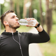 Athletic man drinking water after workout in the park - PhotoDune Item for Sale