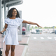 Young african woman waving hand near airport building - PhotoDune Item for Sale