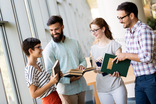 Happy young university students studying with books in library - Stock Photo - Images