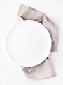 Empty Plate on Linen Napkin on White Table. - PhotoDune Item for Sale