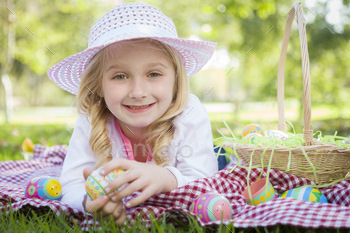 Cute Young Girl on Picnic Blanket Wearing Hat Enjoys Her Easter Eggs Outside in the Park.