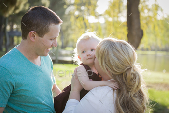 Cute Young Baby Boy Being Hugged By His Parents Outside at the Park.