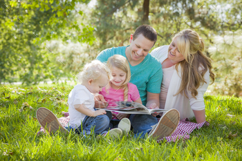 Young Family Enjoys Reading a Book Together in the Park.
