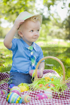 Cute Little Boy Outside On Picnic Blanket Holding Easter Eggs Tips His Hat.
