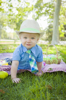 Cute Little Boy Smiles on Picnic Blanket With Easter Eggs Around Him.