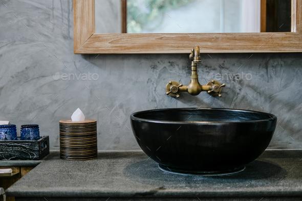 Black sink vintage copper faucet loft bathroom - Stock Photo - Images