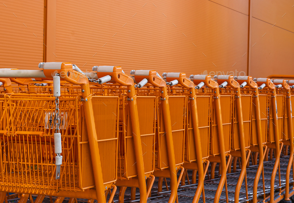 Orange shopping cart stacked by the entrance - Stock Photo - Images