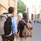Rear View Of Male Gay Couple On Vacation Wearing Backpacks Holding Hands Walking Along City Street - PhotoDune Item for Sale