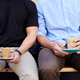 Close Up Of Two Men Sitting Outside Coffee Shop Drinking Coffee - PhotoDune Item for Sale