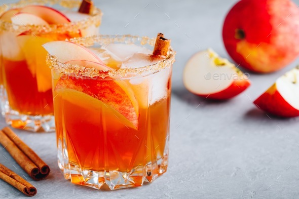 Harvest apple punch with cinnamon and ice for Halloween or Thanksgiving in glass - Stock Photo - Images