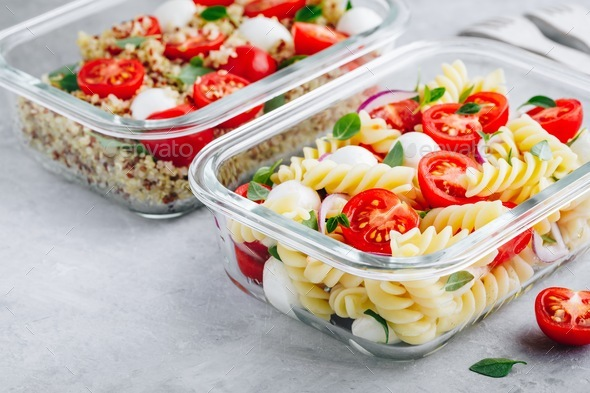 Meal prep containers with pasta salad or quinoa, tomatoes, mozzarella cheese, and basil. - Stock Photo - Images