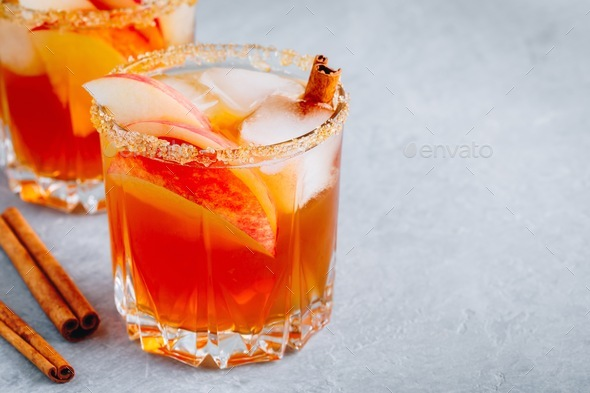 Apple cider margarita with cinnamon and ice for Halloween or Thanksgiving in glass - Stock Photo - Images