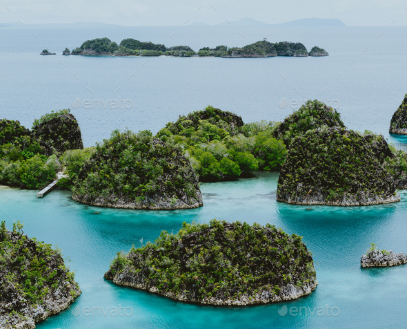Painemo, Group of small island in shallow blue lagoon water, Raja Ampat, West Papua, Indonesia - Stock Photo - Images