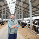 Successful farmer standing in the middle of long aisle inside milk cow farm - PhotoDune Item for Sale