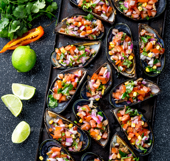 Choros a la chalaca. Big mussels seasoned with purple onion, tomatoes, corn and lemon - Stock Photo - Images