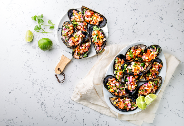 Big mussels, choros zapatos seasoned with purple onion, tomatoes, corn and lemon - Stock Photo - Images