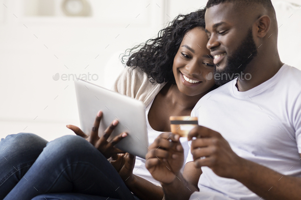 African American Couple Shopping Online Using Digital Tablet At Home - Stock Photo - Images