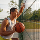 Basketball player standing at the mesh fence - PhotoDune Item for Sale