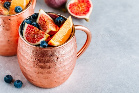 Fig moscow mule ice cold cocktail in copper cup with blueberries and orange - Stock Photo - Images