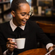 Black african american young yoman drinking coffee and using a t - PhotoDune Item for Sale