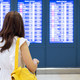 Young woman traveler in the airport looking at the flight information board - PhotoDune Item for Sale