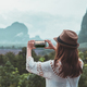 Young woman traveler looking and taking a photo with smartphone at beautiful view - PhotoDune Item for Sale