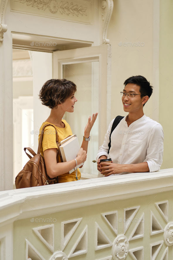 Two young casual smiling international students happily talking at break in corridor of university - Stock Photo - Images