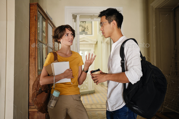 Two young casual international students thoughtfully discussing study in corridor of university - Stock Photo - Images