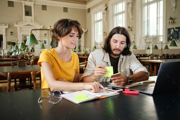 Two young casual students dreamily making notes studying together in library of university - Stock Photo - Images