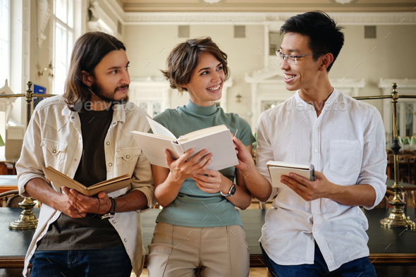Group of young attractive multinational students happily studying together in library of university - Stock Photo - Images