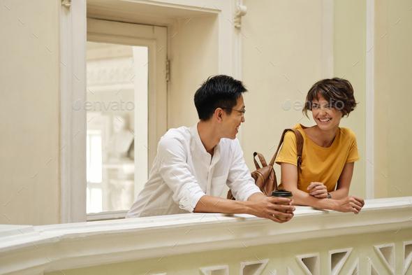 Two smiling international students joyfully talking at break in corridor of university - Stock Photo - Images