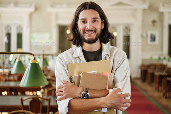 Young cheerful casual male student with notepads joyfully looking in camera in library of university - Stock Photo - Images