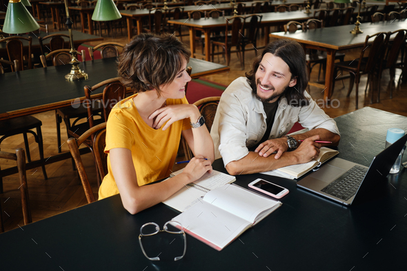 Couple of attractive students happily studying together in library of university - Stock Photo - Images
